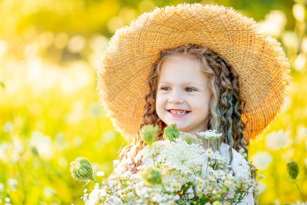 Petite fille heureuse avec un chapeau sur le terrain