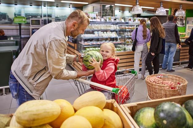 Petite fille heureuse dans le caddie avec le père tient la pastèque