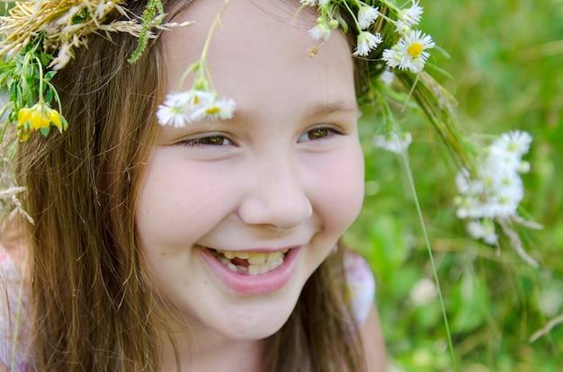 Petite fille heureuse dans une guirlande de fleurs des champs dans le pré