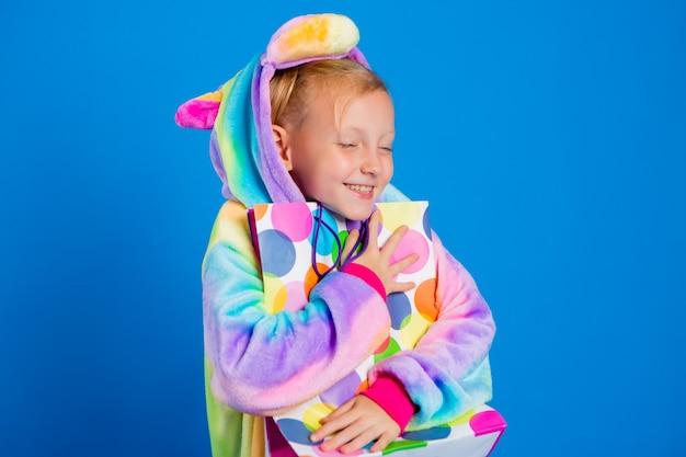 Une petite fille heureuse dans une licorne kigurumi tient un sac cadeau