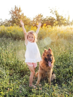 Une petite fille heureuse dans une robe blanche se tient à côté d'un gros chien avec ses mains sur l'herbe verte. berger allemand.