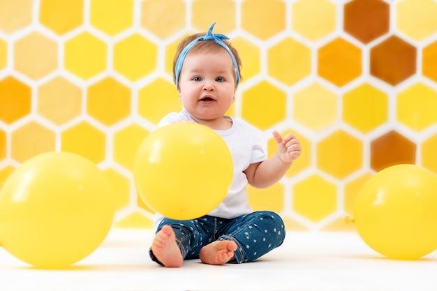 Une petite fille heureuse est assise sur un sol blanc avec des ballons jaunes. en arrière-plan, des nids d'abeilles jaunes. le concept de la journée mondiale des enfants.