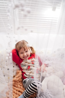 Une petite fille heureuse est couchée dans son lit. chambre des maîtres lumineuse avec un lit à baldaquin est très populaire auprès des enfants. belle detya son pyjama, se prélassant au lit