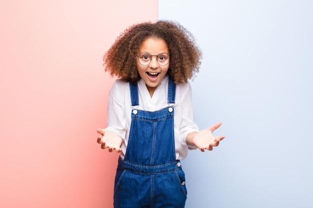 Petite fille heureuse, étonnée, chanceuse et surprise, comme dire sérieusement omg? incroyable sur le mur