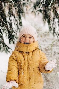Petite fille heureuse avec le jour de la neige en hiver