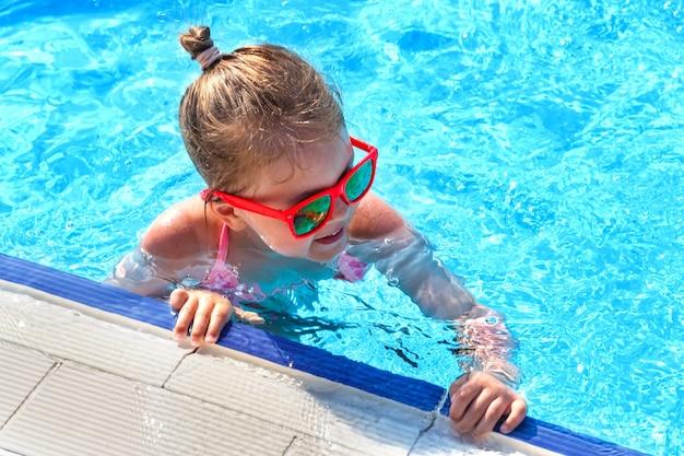 Petite fille heureuse avec des lunettes de soleil nage dans la piscine en été