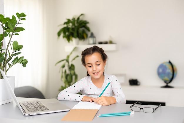 Petite fille heureuse à la maison travaillant avec un ordinateur portable