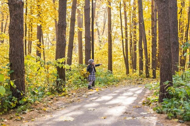 Petite fille heureuse marchant dans le parc automne