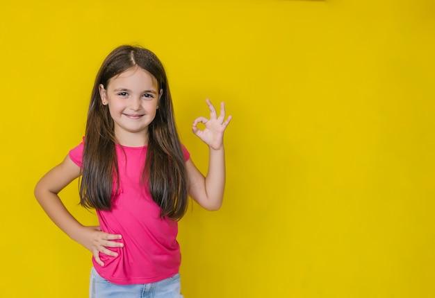 Une petite fille heureuse mignonne regardant et montrant un signe d'approbation, ok.