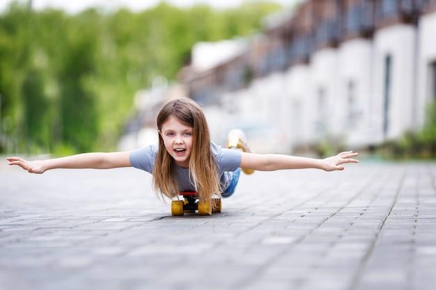 Une petite fille heureuse monte joyeusement sur le ventre sur une planche à roulettes dans la rue en été