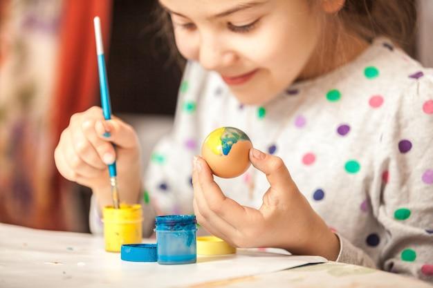 Petite fille heureuse peignant l'oeuf de pâques