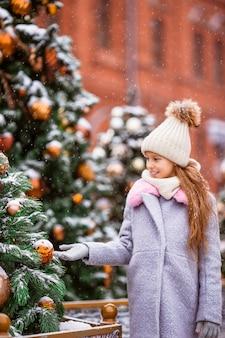 Petite fille heureuse près de branche de sapin dans la neige pour le nouvel an.