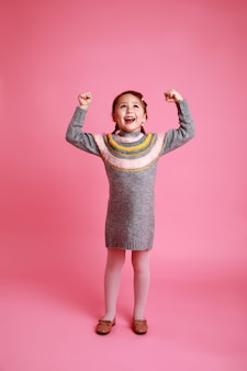 Petite fille heureuse en robe chaude montrant sa force sur fond rose