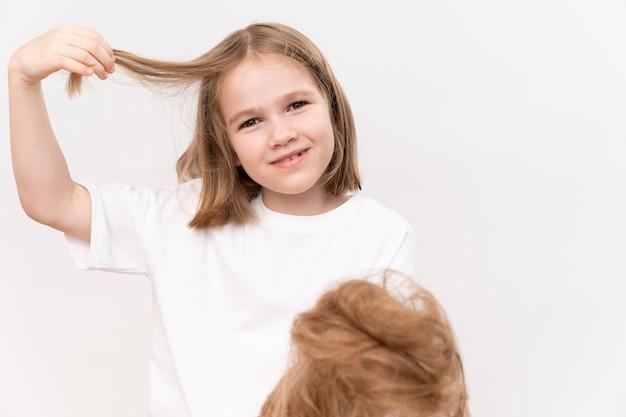 Une petite fille heureuse tient dans les mains les cheveux coupés après avoir coupé sur un fond blanc. signifie prendre soin des cheveux des enfants. salon de beauté pour enfants.