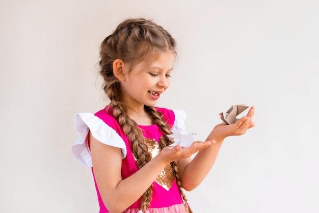 Une petite fille heureuse tient deux oiseaux en papier.