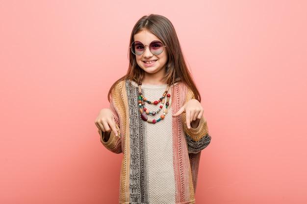 Petite fille hippie pointe avec les doigts, sentiment positif.