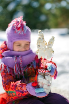 Petite fille en hiver dans une forêt enneigée boit du chocolat chaud noël et bonhomme de neige