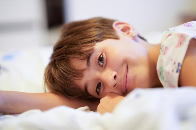 Petite fille de huit ans allongée sur son lit