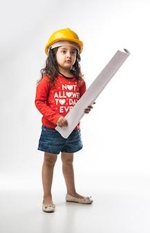 Petite fille indienne ingénieur avec un casque jaune et un rouleau de papier à dessin ou un plan, isolé sur fond blanc