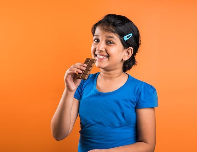 Petite fille indienne mangeant une plaque de chocolat, isolée sur fond orange