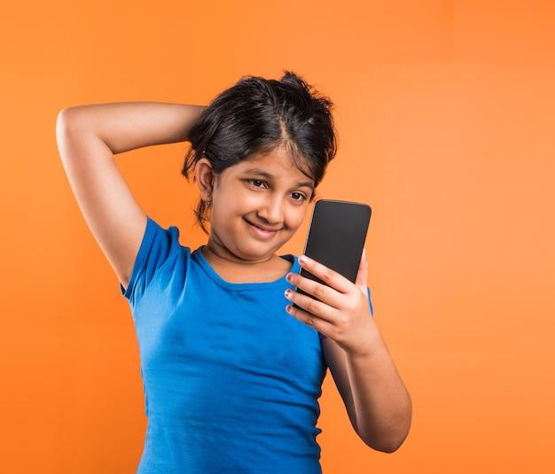 Petite fille indienne mignonne avec le smartphone, jouant ou cliquant sur le selfie