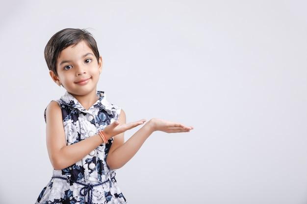 Petite fille indienne montrant quelque chose avec ses mains. fond