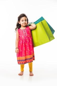 Petite fille indienne tenant des sacs à provisions, debout isolé sur fond blanc