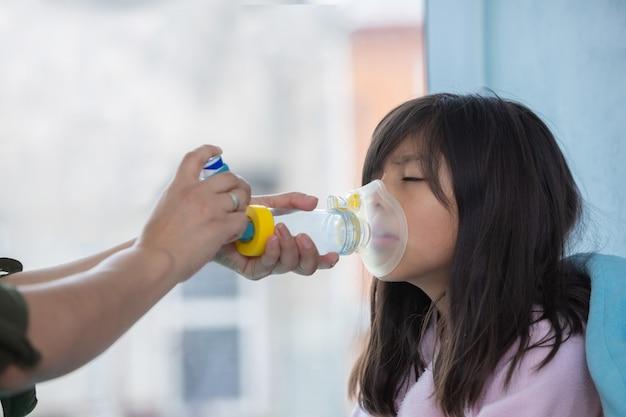 Petite fille avec inhalateur pour l'asthme