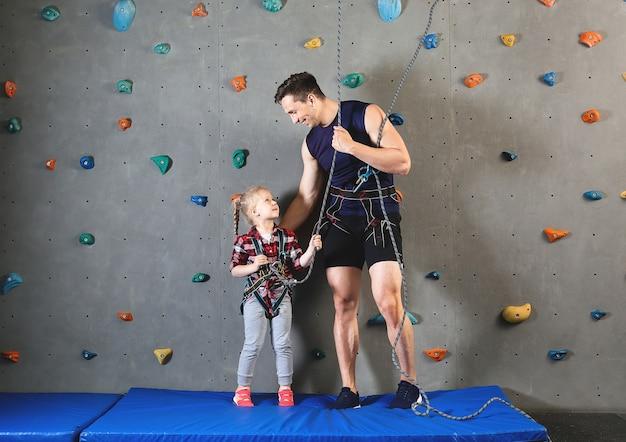 Petite fille avec instructeur en salle d'escalade