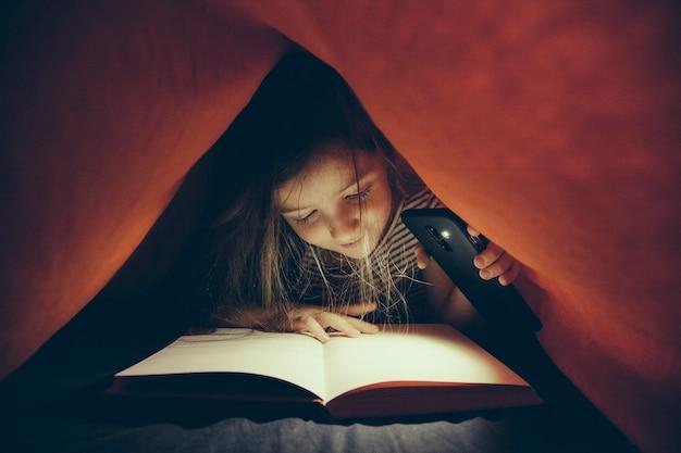 Petite fille intelligente étudie dans l'obscurité