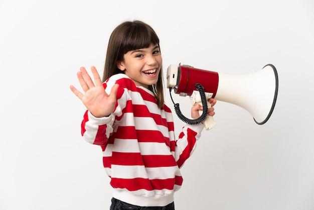Petite fille isolée sur fond blanc tenant un mégaphone et saluant avec la main avec une expression heureuse