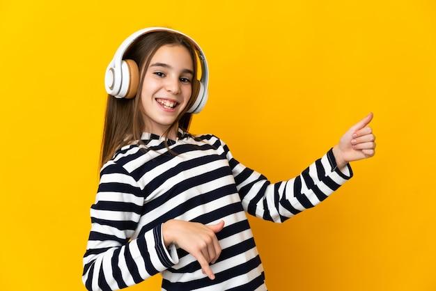 Petite fille isolée sur fond jaune, écouter de la musique et faire un geste de guitare