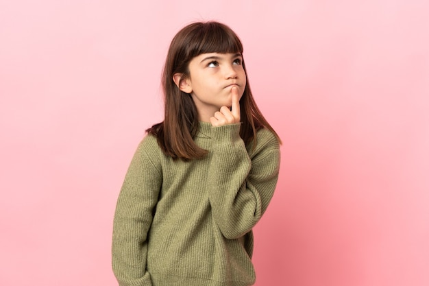 Petite fille isolée sur fond rose ayant des doutes en levant les yeux