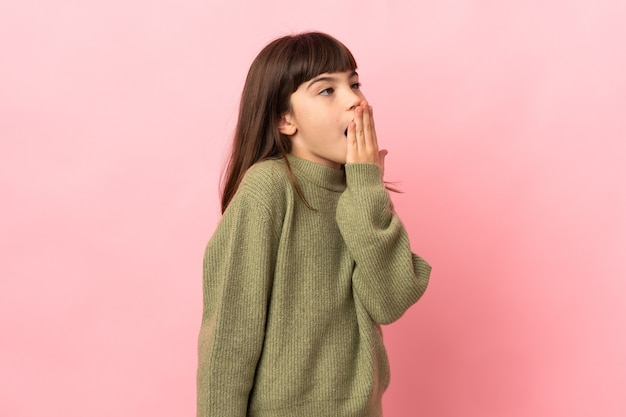 Petite fille isolée sur fond rose bâillant et couvrant la bouche grande ouverte avec la main