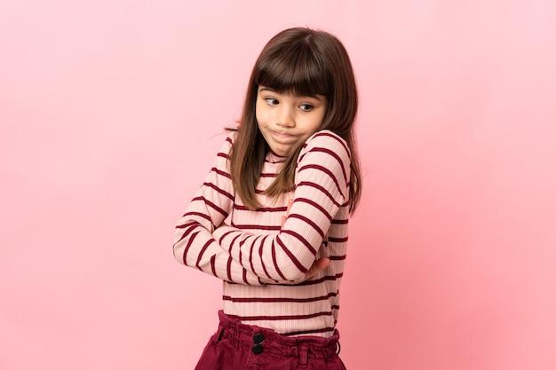Petite fille isolée sur fond rose faisant un geste de doute tout en soulevant les épaules