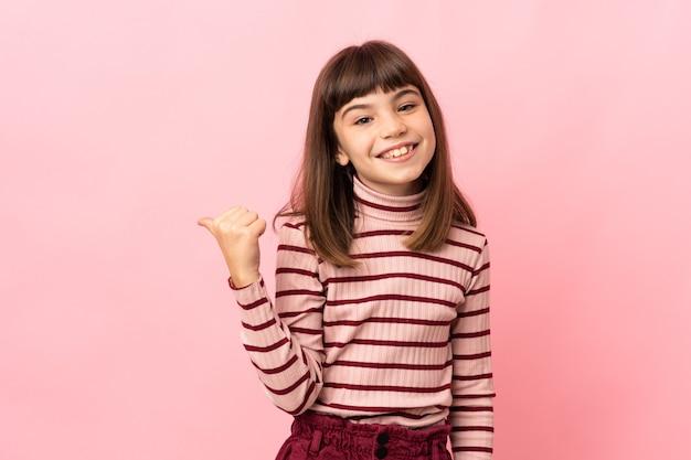 Petite fille isolée sur fond rose pointant vers le côté pour présenter un produit