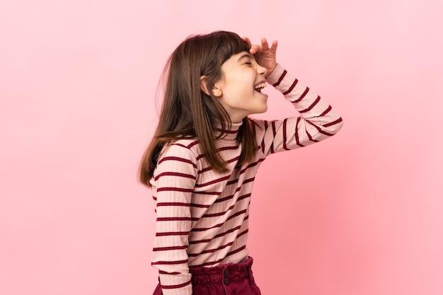 Petite fille isolée sur fond rose souriant beaucoup