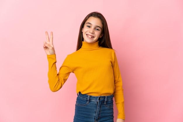 Petite fille isolée sur fond rose souriant et montrant le signe de la victoire