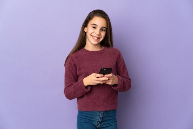Petite fille isolée sur fond violet envoyant un message avec le mobile