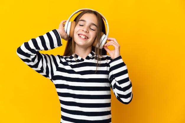 Petite fille isolée sur un mur jaune à l'écoute de la musique et du chant
