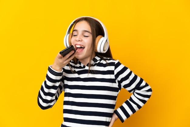 Petite fille isolée sur un mur jaune, écouter de la musique avec un mobile et chanter