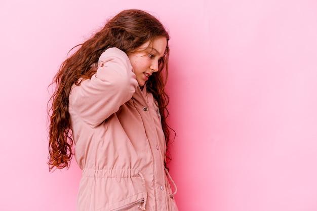 Petite fille isolée sur un mur rose ayant une douleur au cou due au stress, en massant et en la touchant avec la main