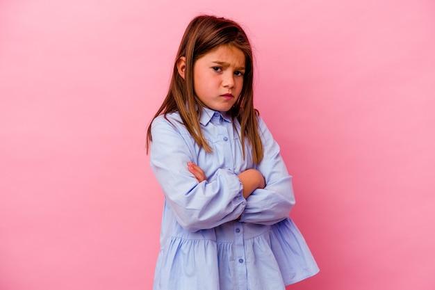 Petite fille isolée sur un mur rose malheureux à la recherche à huis clos avec une expression sarcastique