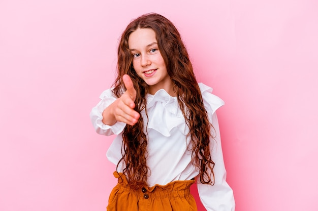 Petite fille isolée sur un mur rose qui s'étend la main à la caméra en geste de salutation