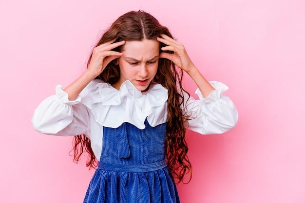 Petite fille isolée sur un mur rose touchant les tempes et ayant mal à la tête