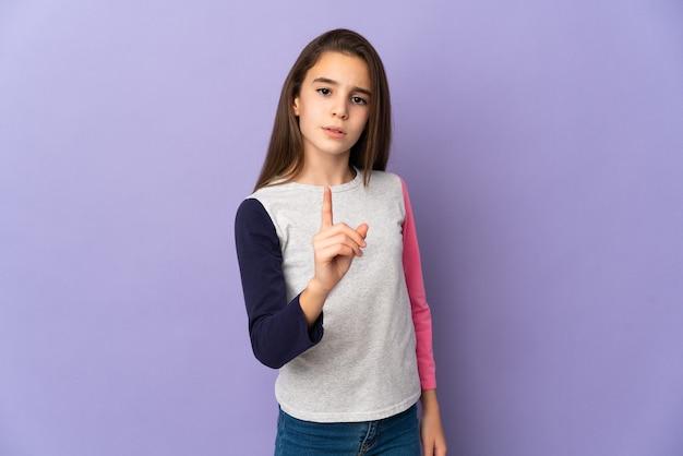 Petite fille isolée sur un mur violet frustré et pointant vers l'avant