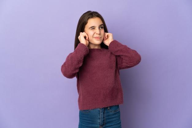 Petite fille isolée sur violet frustré et couvrant les oreilles