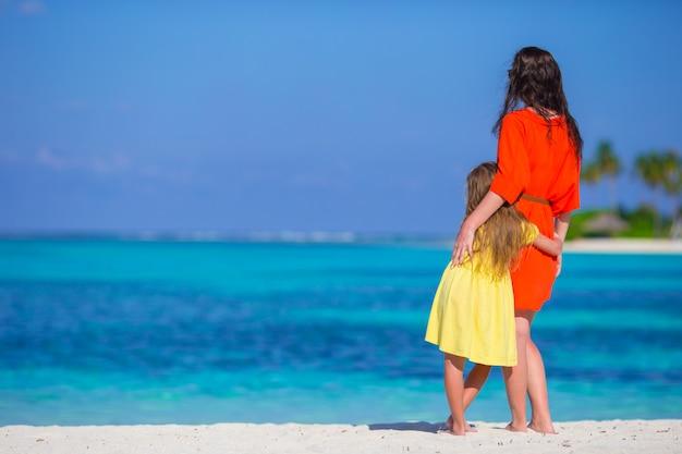 Petite fille et jeune maman pendant les vacances à la plage