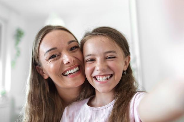 Petite fille jeune mère face webcam vue rapprochée. une adorable petite fille utilise un smartphone pour s'amuser avec sa sœur aînée en faisant des selfies, les vloggers enregistrent un nouveau vlog, profitent d'un concept d'activité amusant