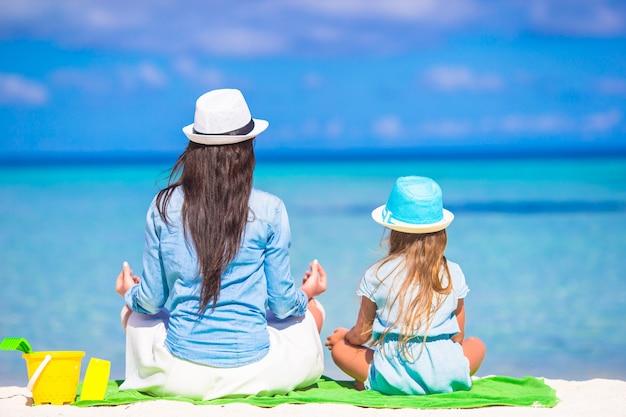 Petite fille et jeune mère se détendre à la plage pendant des vacances tropicales